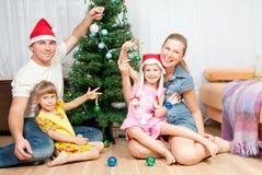 Familia bajo la picea de la Navidad Fotos de archivo libres de regalías