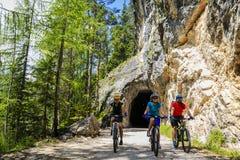 Familia biking de la montaña con las bicis en la pista, ` Ampezzo, D de la cortina d fotografía de archivo