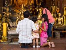Familia budista asiática que hace las ofrendas en el templo en Ayutthaya, T foto de archivo libre de regalías