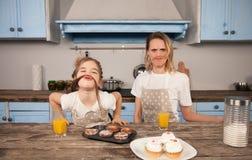 Familia cariñosa feliz en la cocina La muchacha de la hija de la madre y del niño está comiendo las galletas que han hecho y d imagen de archivo