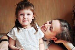 Familia cariñosa feliz muchacha de la madre y del niño que juega y que abraza foto de archivo