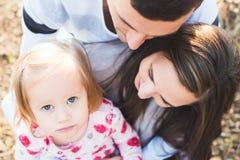 Familia cariñosa joven de tres, retrato sincero auténtico de la familia del aire libre foto de archivo