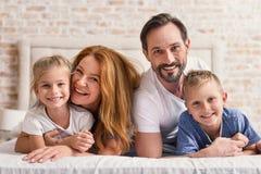 Familia cariñosa que miente en cama Fotos de archivo libres de regalías