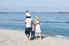 Familia cariñosa que recorre en la arena Fotografía de archivo libre de regalías