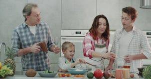 Familia carismática en el fin de semana que cocina el desayuno junto en una cocina moderna, gasto de cuatro miembros de la famili almacen de metraje de vídeo