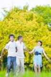 Familia caucásica de tres que se divierten junto y que corren en bosque del verano Imagen de archivo