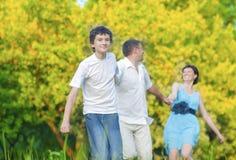 Familia caucásica de tres que se divierten junto y que corren en bosque del verano Fotografía de archivo libre de regalías
