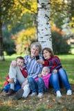 Familia caucásica en parque que fotografía en el teléfono móvil Selfie Foto de archivo libre de regalías