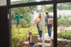 Familia caucásica feliz con las cajas de cartón que camina hacia hogar imagen de archivo