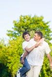 Familia caucásica feliz de padre y de hijo que llevan a cuestas al aire libre Contra bosque del verde de la naturaleza Fotos de archivo libres de regalías