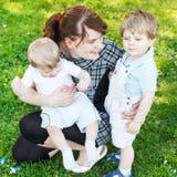 Familia caucásica feliz de tres: Madre joven y dos poco sib foto de archivo libre de regalías