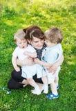 Familia caucásica feliz de tres: Madre joven y dos poco sib fotografía de archivo