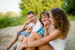 Familia caucásica feliz que come la barra de chocolate junto Fotografía de archivo libre de regalías