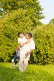 Familia caucásica feliz de padre y de hijo que llevan a cuestas al aire libre Imagenes de archivo