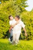 Familia caucásica feliz de padre y de hijo que llevan a cuestas al aire libre Foto de archivo libre de regalías