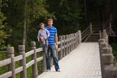 Padre e hijo cerca de la cerca en parque Imágenes de archivo libres de regalías