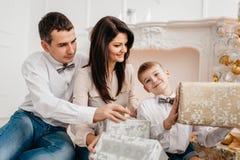 Familia cerca de la chimenea con los regalos de Navidad Imagen de archivo libre de regalías