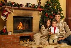 Familia cerca de la chimenea en casa de la Navidad Imagenes de archivo