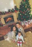 Familia cerca de la chimenea en interior adornado de la casa Fotos de archivo libres de regalías