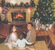 Familia cerca de la chimenea en interior adornado de la casa Imagen de archivo libre de regalías