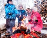 Familia cerca de la hoguera en paisaje del invierno Imagen de archivo libre de regalías