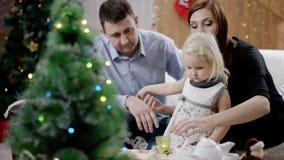 Familia cerca de un árbol de navidad, niño que va al abeto almacen de video