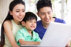 Familia china en el escritorio usando la computadora portátil Fotos de archivo