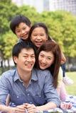 Familia china joven que se relaja en parque junto Imagen de archivo