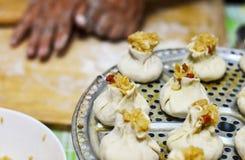 Familia china que hace las bolas de masa hervida del arroz de Shaomai Foto de archivo