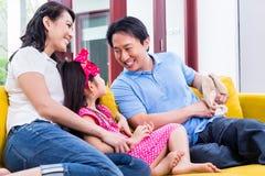 Familia china que juega con la hija en el sofá fotografía de archivo libre de regalías