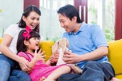 Familia china que juega con la hija en el sofá Fotos de archivo