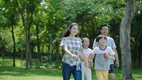 Familia china que sonríe y que camina junto en parque Fotografía de archivo libre de regalías