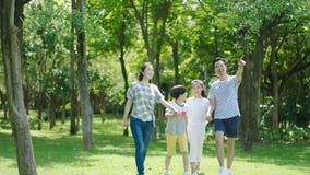 Familia china que sonríe y que camina junto en parque mientras que padre que señala a la distancia Imagen de archivo