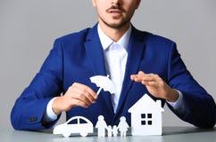 Familia, coche y hogar masculinos del papel de cubierta del agente de seguro con el recorte del paraguas en la tabla fotografía de archivo