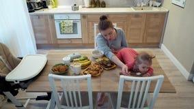 Familia, comida, niño, nutrición y concepto de la paternidad - madre joven feliz que desayuna con el bebé que se sienta encendido almacen de metraje de vídeo