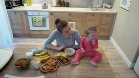 Familia, comida, niño, nutrición y concepto de la paternidad - madre joven feliz que desayuna con el bebé que se sienta encendido metrajes