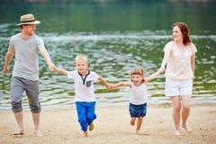 Familia con dos niños en la playa Foto de archivo libre de regalías