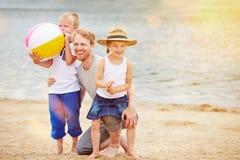 Familia con dos niños en la playa el vacaciones Imagen de archivo libre de regalías