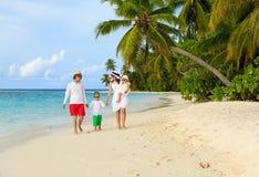 Familia con dos niños que caminan en la playa tropical Imágenes de archivo libres de regalías