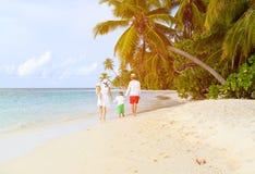 Familia con dos niños que caminan en la playa tropical Fotos de archivo libres de regalías