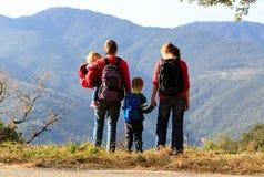 Familia con dos niños que caminan en montañas Fotos de archivo libres de regalías