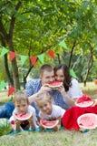 Familia con dos niños que comen las sandías en la comida campestre al aire libre Imagen de archivo