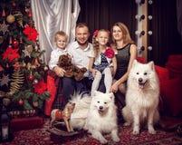 Familia con dos perros blancos cerca del árbol de navidad Imagen de archivo libre de regalías