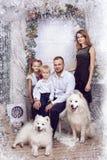 Familia con dos perros blancos cerca del árbol de navidad Imagen de archivo