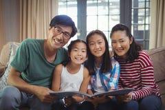 Familia con el álbum de foto junto en sala de estar Foto de archivo libre de regalías