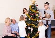 Familia con el árbol de navidad adornado Imágenes de archivo libres de regalías