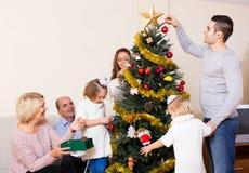Familia con el árbol de navidad adornado Fotos de archivo
