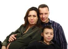 Familia con el abrazo embarazado de la madre Foto de archivo libre de regalías