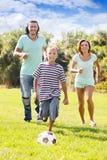 Familia con el adolescente que juega en fútbol Fotografía de archivo libre de regalías