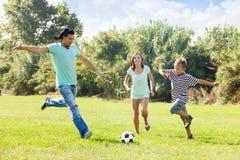 Familia con el adolescente que juega en fútbol Imagenes de archivo
